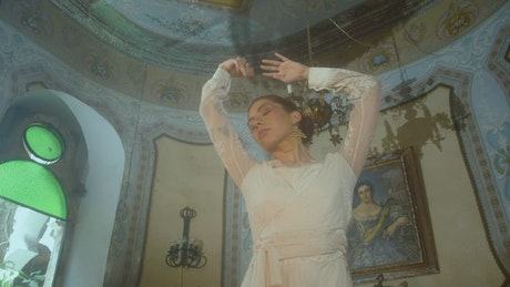 A redhead woman is dancing and modeling in a victorian ballroom
