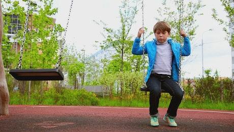 A sad boy sitting on the swings