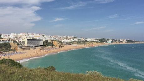 A sandy beach with a white city