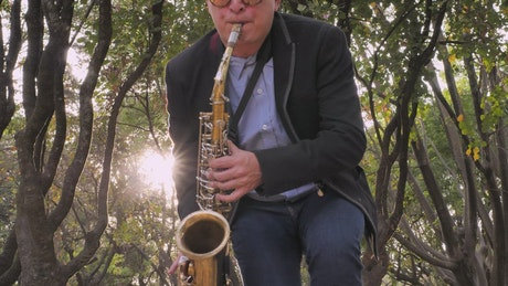 A saxophonist dances while playing