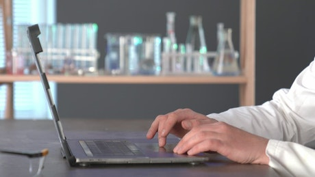 A Scientist typing on a laptop in the lab