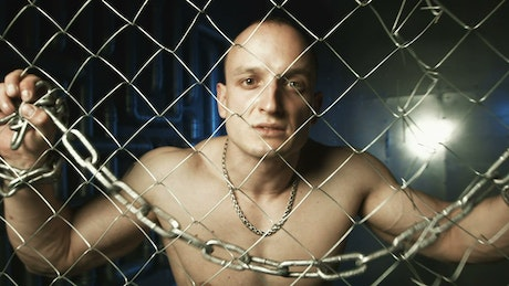 A shirtless man with metal chain behind the fence