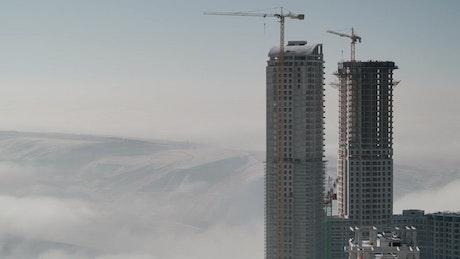 A skyscraper under costruction above the clouds