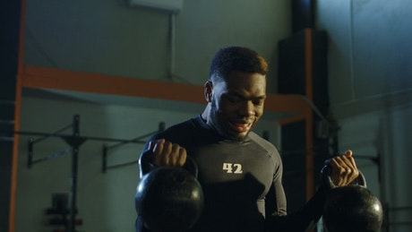 A strong man lifting kettlebells in the gym
