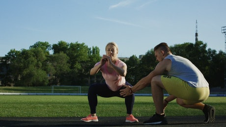A trainer helps a woman with the squats training