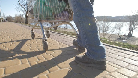 A tramp walking in the sun with a metal cart