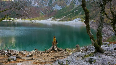 A woman and a crystal water lake in the mountains