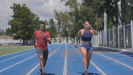 A woman and a man exercising on a running track