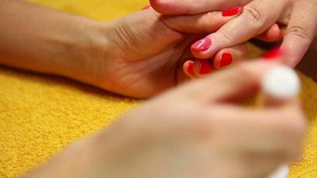 A woman applying red nail polish