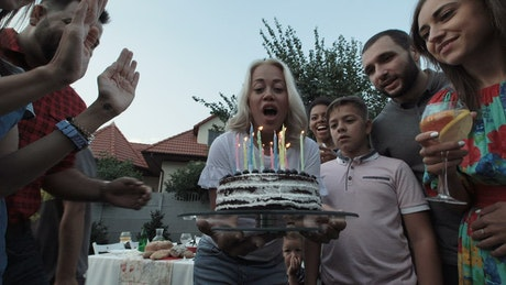 A woman blows the candles in a birthday party