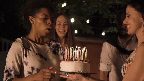 A woman blows the candles of the cake