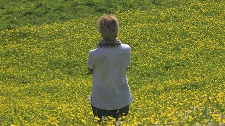 A woman contemplates a yellow flower field