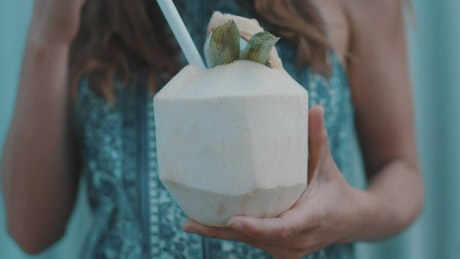A woman drinking coconut water with a straw