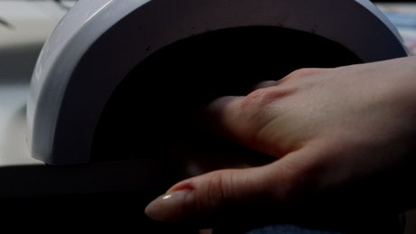 A woman hand in a UV lamp