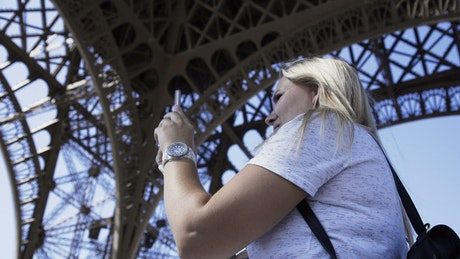 A woman making a video call under the Eiffel tower