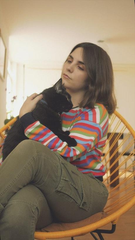 A woman petting a black cat