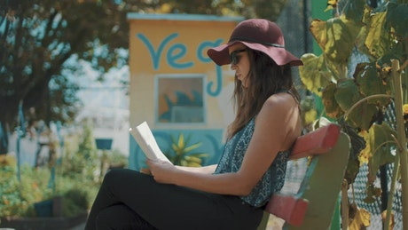 A woman reading a book outdoors