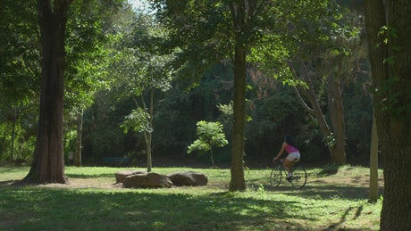 A woman riding her bicycle at a green park