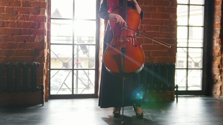 A woman standing in a room playing the Cello