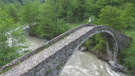 A woman standing in an old stone bridge above the river