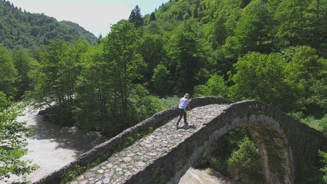 A woman standing on a bridge over a stream
