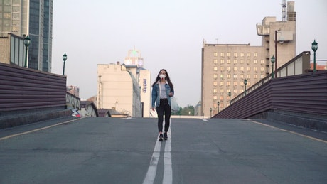 A woman walking in the middle of an empty street
