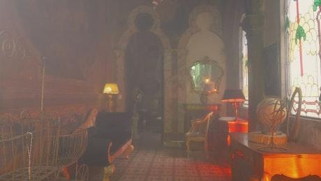 A woman walking through a vintage house corridor