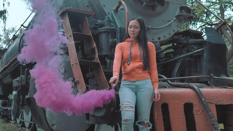 A woman waving a smoke bomb on a train