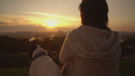 A woman with her dog watching the sunset