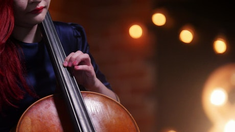 A woman with red hair plays the Cello