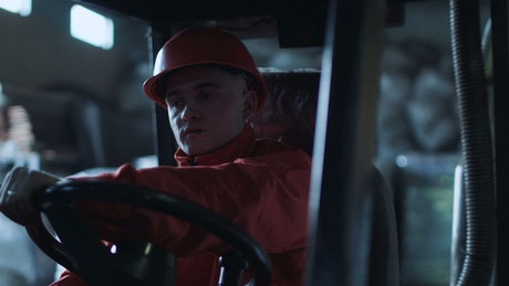 A worker driving through the warehouse