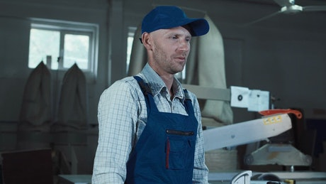 A worker in overalls looking at the camera