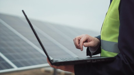 A worker with a laptop or on a solar panel field