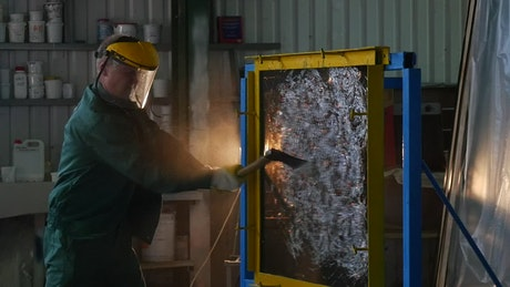 A worker with protective uniform hitting a glass sheet