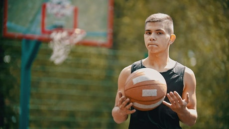 A young man holding a basketball ball
