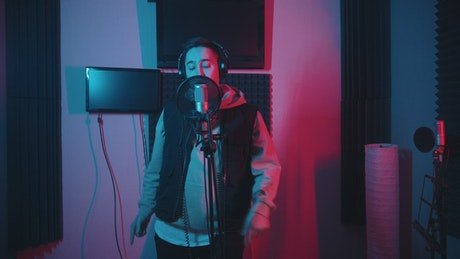 A young man in hoodie rapping in the studio