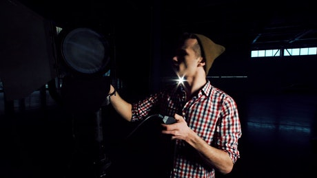 A young man turns on a studio light