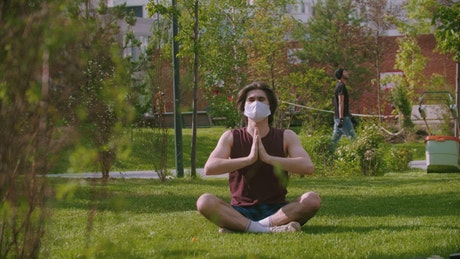 A young man wearing a medical mask meditating on the park