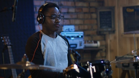 A young man with headphones playing the drums