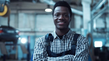A young mechanic is smiling to the camera