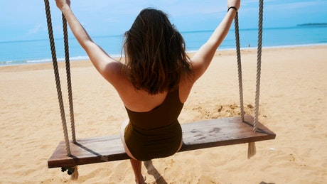 A young woman enjoying a swing on the beach