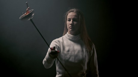 A young woman fencer playing with her sword