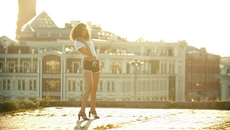 A young woman in small shorts performing a sexy and attractive  dance on a roof