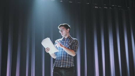 Actor reading his script on stage