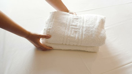 Adding clean towels to a hotel bed