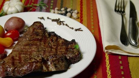 Adding fresh herbs to a steak