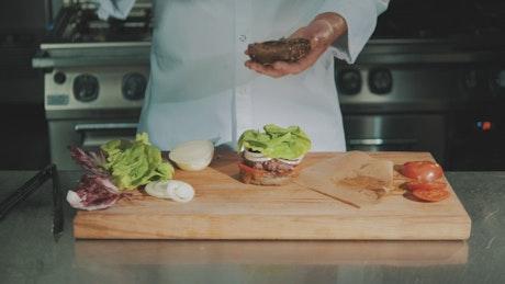 Adding sauce to a burger
