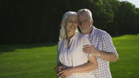 Adult man and woman embracing on a meadow