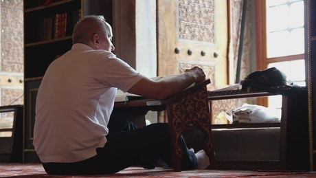Adult man reading the Quran inside a mosque