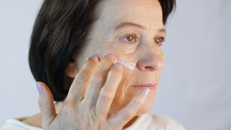 Adult woman gently putting a cream on her face